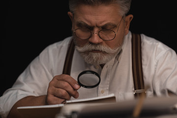 close-up portrait of senior writer reading manuscript in notebook with magnifying glass