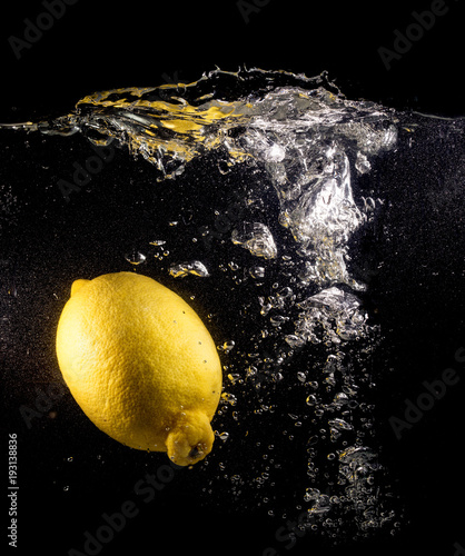 Yellow lemon in water on a black background - 193138836