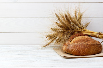 Rustic bread and wheat on an old vintage planked wood table. free text space