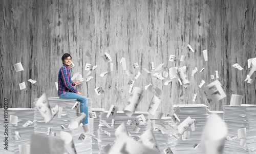 Attractive man sitting on pile of paper documents.