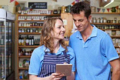 Staff In Delicatessen Using Digital Tablet