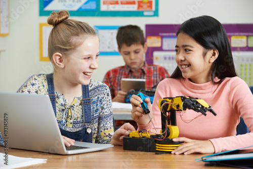 Two Female Pupils In Science Lesson Studying Robotics