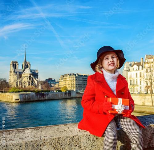 girl on embankment near Notre Dame de Paris with Christmas gift ...