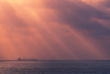 sunrays on the ocean with freighter ship - 193151228