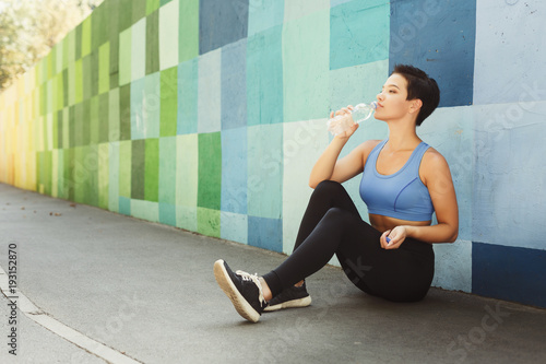 Woman runner is having break, drinking water