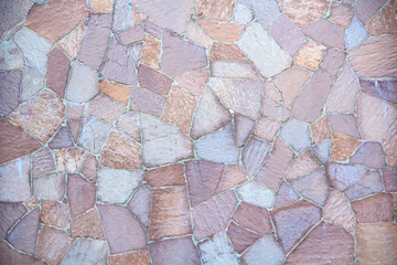 The texture of a beautiful fence with pieces of colored decorative stone.