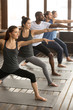 Leinwanddruck Bild - Group of young sporty afro american and caucasian people practicing yoga lesson, standing in Warrior two exercise, Virabhadrasana II pose, working out, indoor, studio