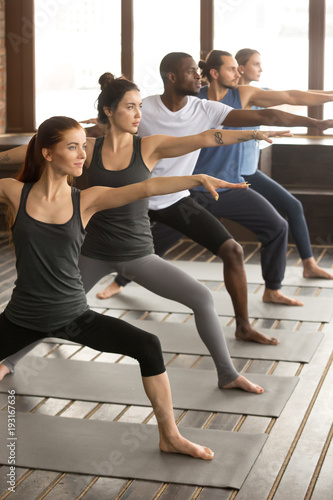 Leinwanddruck Bild Group of young sporty afro american and caucasian people practicing yoga lesson, standing in Warrior two exercise, Virabhadrasana II pose, working out, indoor, studio
