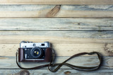 Old vintage film photo camera with brown leather strap on grunge wooden table. Photographe concept background - 193167802