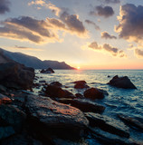 Picturesque seascape on beauty seacost. Rocky beach and waves glowing by sunrice light. Vacations travel concept - 193168057