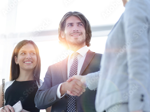 Businesspeople  shaking hands against room with large window loo - 193168075
