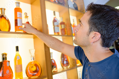 Man selecting bottle of brandy from shelf