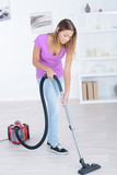 ordinary housewife in casual dress hoovering surfaces - 193174020