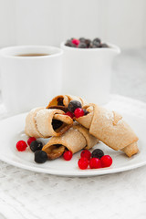 sweet bagels cookies and berries on a plate with two white cups