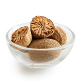 Dried whole and cut nutmegs in glass bowl isolated on white. - 193177023