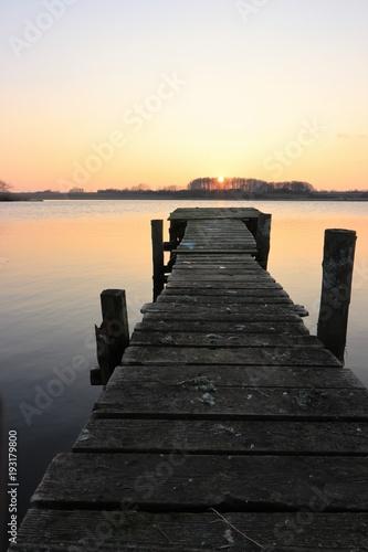 idylliczna kładka nad jeziorem o zachodzie słońca