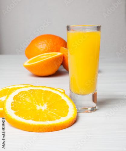 Orange juice glass and orange slices on a light wood background