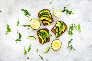 Have a bite with healthy snacks. Avocado toast on grey background top view
