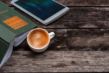 Cup of hot coffee,green book and white tablet on wooden table background