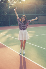 portrait cheerful asian younger woman in tennis court happiness emotion