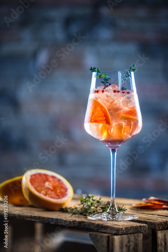 Cocktail drink on a old  wooden board. Alcoholic beverage with tropical fruits red pepper herb and ice