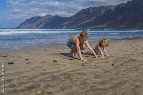 Papiers peints Iles Canaries Children, a boy and a girl, playing with the sand at Famara beach, Lanzarote, Spain