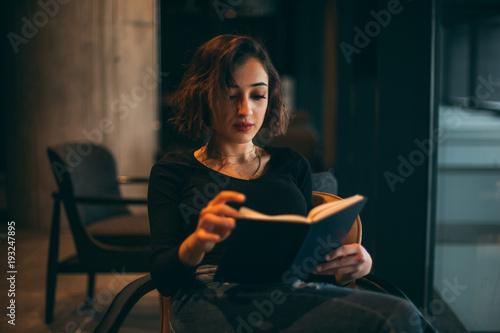 Fototapeta Young, Urban Girl Sitting in Cafe, Reading Book