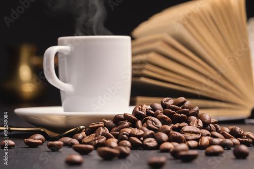 Fotobehang Koffiebonen Open book, white cup of coffee, coffee beans. Dark background. Copy space.