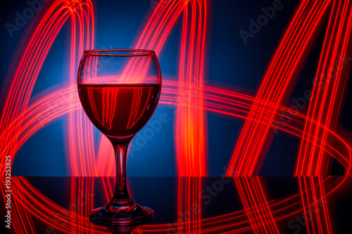 Fototapeta A glass of red wine closeup on the background of bright lights..