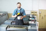 Portrait of a handsome typographer standing with yellow paint for offset machine at the printing manufacturing