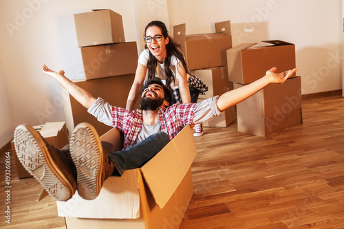 Young couple moving into a new home.Man sitting in cardboard box while woman pushes him all over the room.Real estate funny concept.