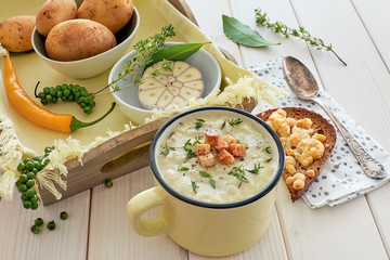 Homemade cream of potato soup with croutons and thyme, served with bread toasted with cheese