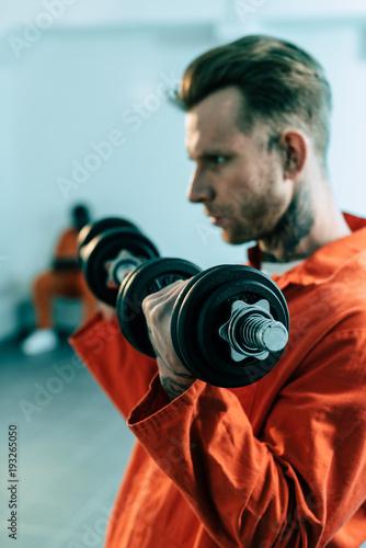 prisoner training with dumbbells in prison cell