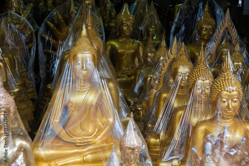 Aluminium Bangkok Golden Buddha statue wrapped in plastic, in a shop in Bangkok