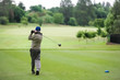 Man teeing off on a golf course with a driver