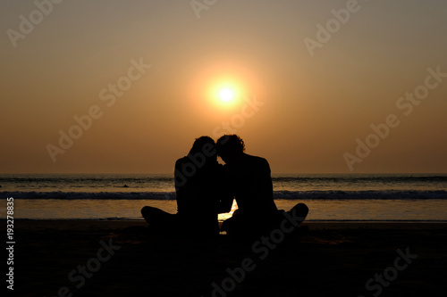 Foto Murales Couple's silhouette hugging on the beach at sunset