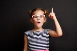 Child having idea. Pretty girl in glasses posing with finger up over blackboard. - 193284027