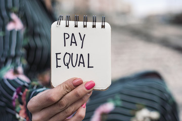woman and the text pay equal in a piece of paper