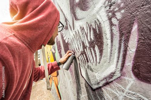 Uliczny artysta maluje colourful graffiti na jawnej ścianie - sztuki współczesnej pojęcie z miastowym facetem wykonuje i przygotowywa żyć murales z wielobarwną aerosolową kiścią - światło słoneczne filtr z ostrością na potworze