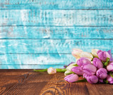 Bouquet of colored tulips placed on vintage wooden planks