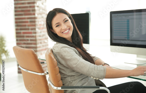 young employee of the company works with computer data.