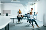 Office. People Having Fun And Racing On Chairs. - 193301699