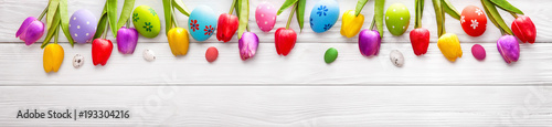 Easter Colored Eggs with Flowers on White Wood Background