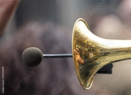 Brass trumpet, front side with microphone for loud sound. Close up view with details, blurred background.