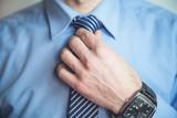 Caucasian man fixing his tie.