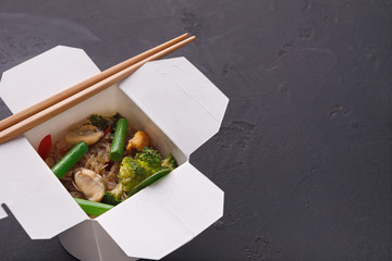 Asian food in delivery box on gray background
