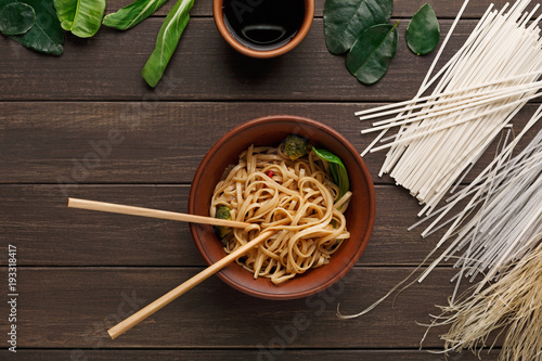 Fototapeta Bowl of rice noodles with soy souce on wooden background