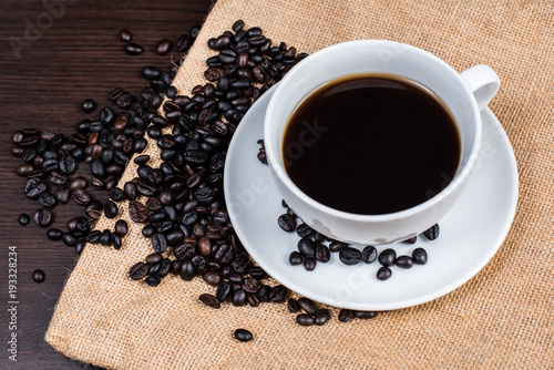 Fotobehang Koffiebonen Black coffee in white cup and coffee bean on cloth and wood background.