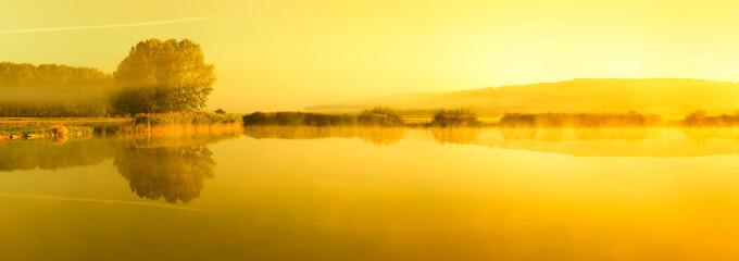 Stiller See bei Sonnenaufgang mit Nebelschwaden