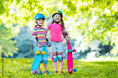 Fotobehang Skateboard Children riding skateboard in summer park
